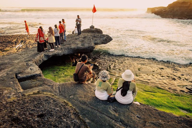 People sitting on rocks at beach