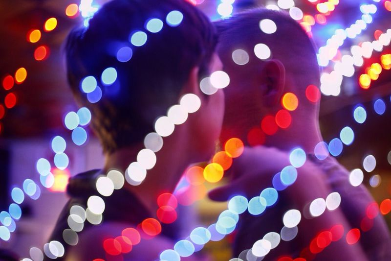 Illuminated Colorful Defocused Lights Against Man And Woman In Bar