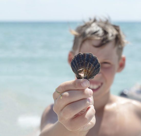 The boy holds a seashell in his hand. the face of a teenager against  the sea. smile.