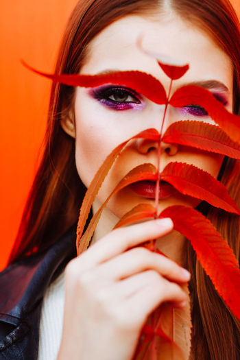 Close-Up Portrait Of Young Woman Holding Leaves Against Face