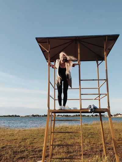 Woman standing in lifeguard hut at beach against sky