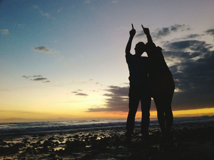 Silhouette couple gesturing at beach during sunset