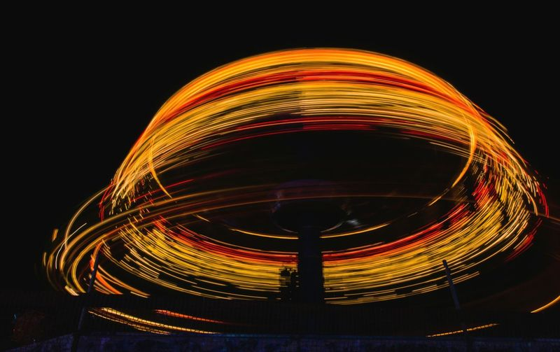 Light trails at amusement park against sky at night