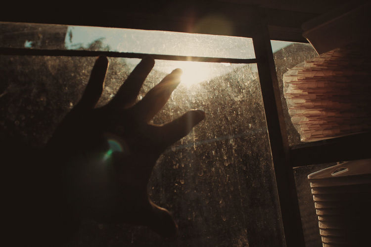Close-up of hand on window