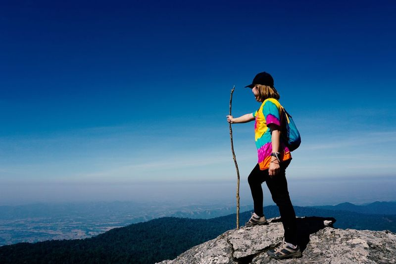 Full length of woman holding stick while standing on mountain against sky