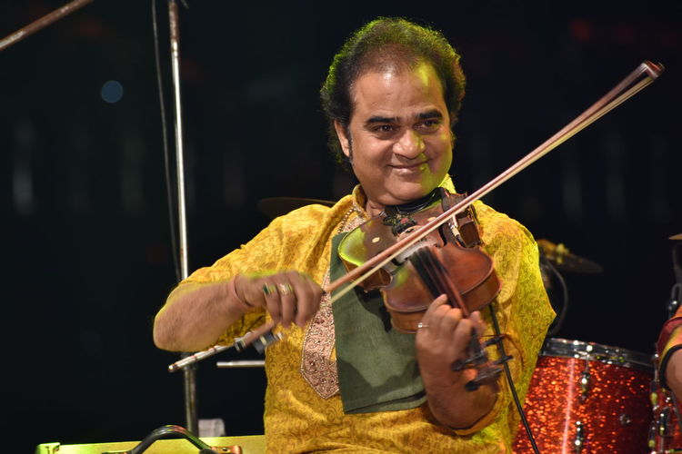 Smiling man playing violin while sitting on stage
