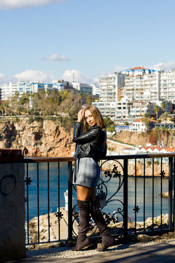 Young woman standing on railing against cityscape