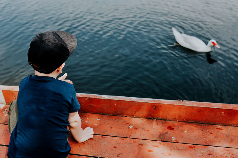 Rear view of boy sitting on boat against sea