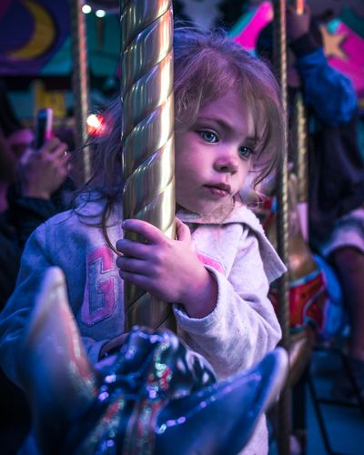 Little girl on a carousel 🎠 neon lighting. Neon Lights Neon Circus Childhood Child Girls Looking At Camera Innocence Females Portrait One Person Leisure Activity Women Offspring Casual Clothing Amusement Park Holding Cute Looking Front View Real People Hairstyle