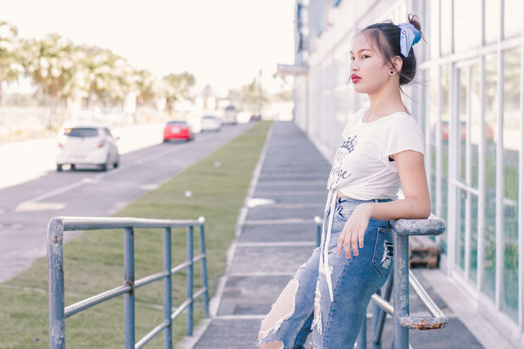 Beautiful Woman Car Casual Clothing City Day Focus On Foreground Hairstyle Land Vehicle Leisure Activity Lifestyles Looking Away Mode Of Transportation Motor Vehicle One Person Outdoors Railing Real People Side View Three Quarter Length Transportation Young Adult
