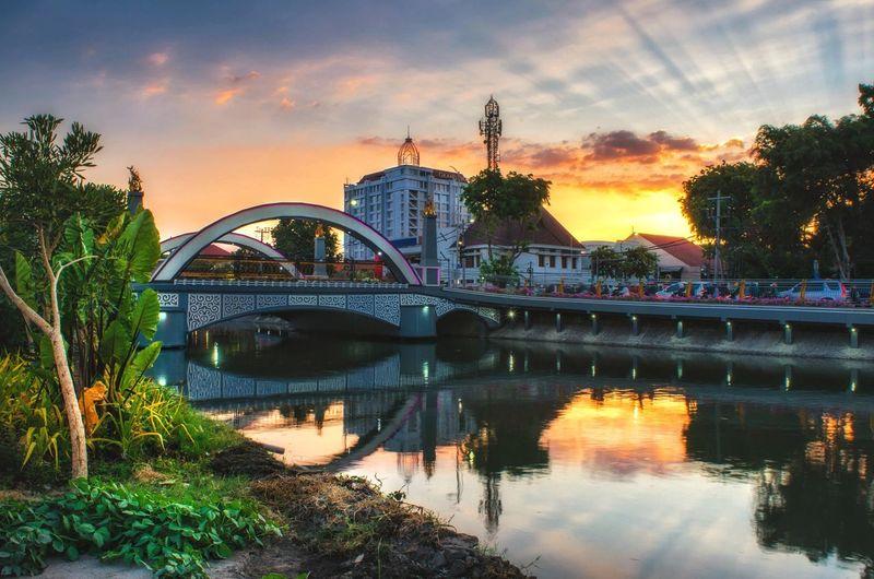 Bridge over river in city against orange sky