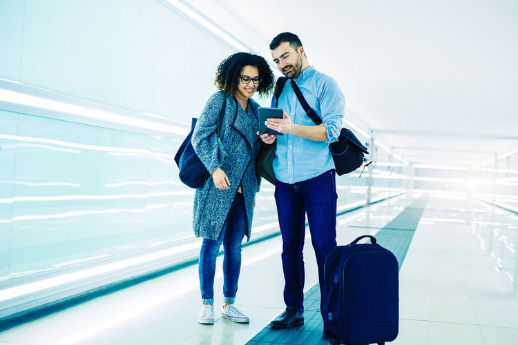 Adult Airport Airport Terminal Casual Clothing Couple - Relationship Emotion Full Length Happiness Luggage Men Mid Adult Positive Emotion Smiling Togetherness Transportation Travel Two People Women Young Adult Young Men Young Women