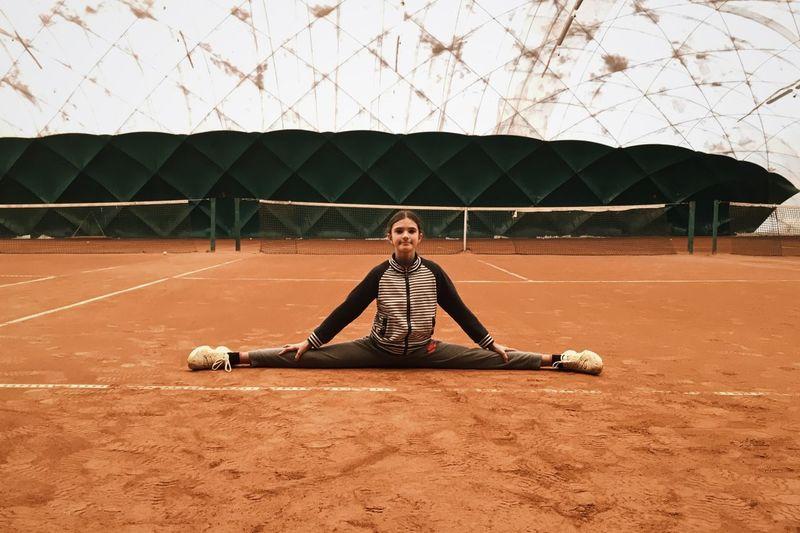 Full length of woman doing split on field