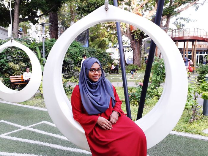 Portrait of smiling young woman wearing hijab sitting on swing in park