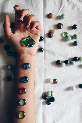 Cropped hands of woman with gemstones on sheet