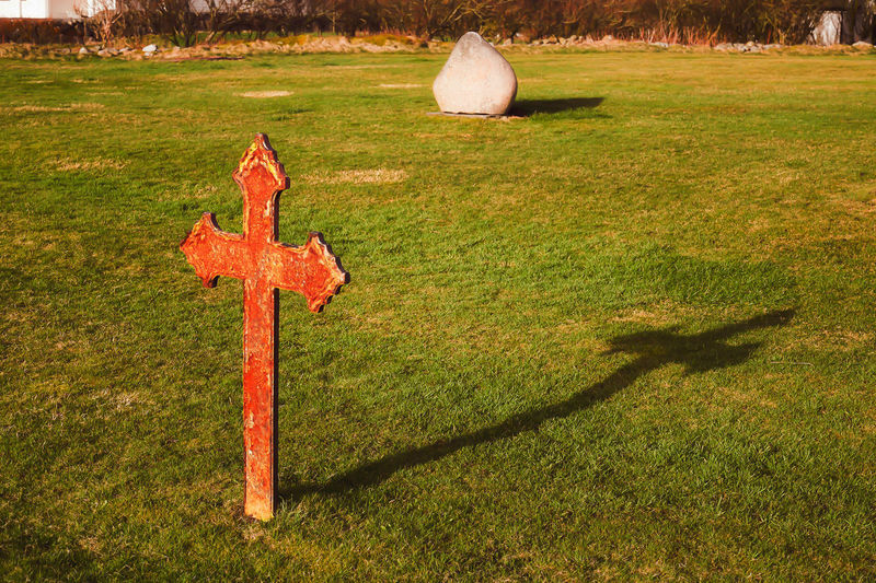 Grass Religion Belief Plant Nature Shadow Spirituality Day Cross Green Color No People Sunlight Cemetery Tombstone Grave Field Land Outdoors Stone Symbol