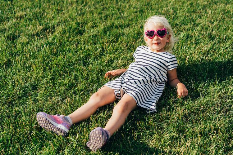 Boy wearing sunglasses on grassy field