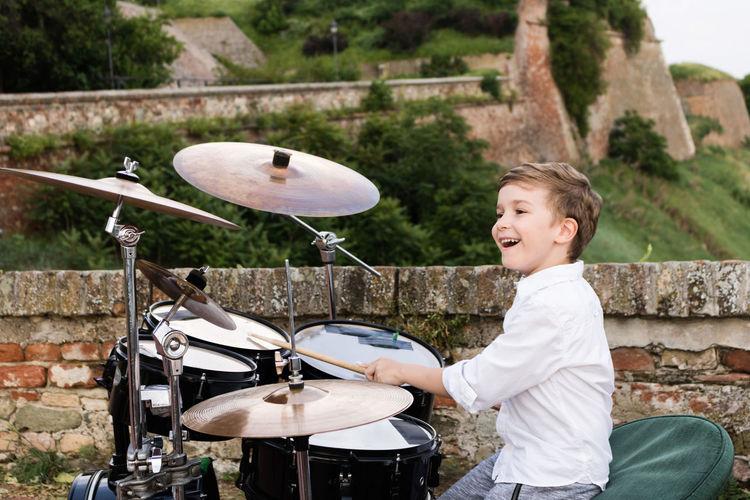 Smiling boy playing drum kit outdoors