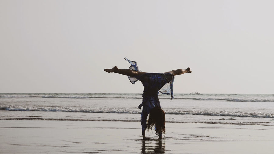 Rear view of woman performing hand stand on shore against sky