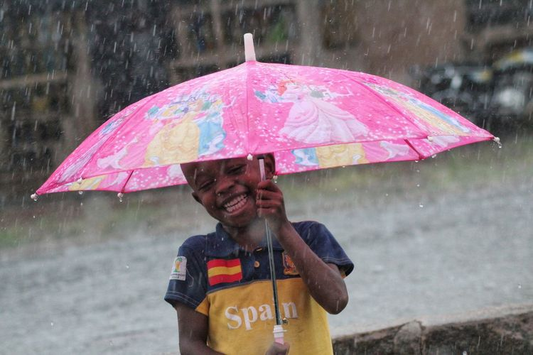 Happy Boy Holding Umbrella During Rainy Season