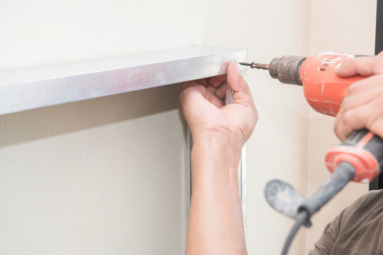Cropped Hands Drilling Metal On Wall