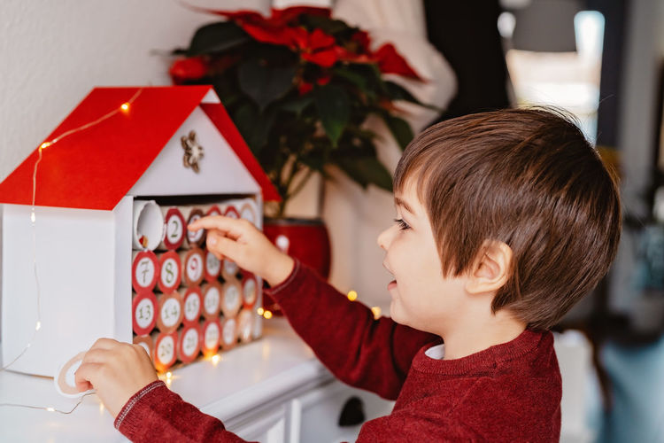 Portrait of boy holding christmas decoration at home