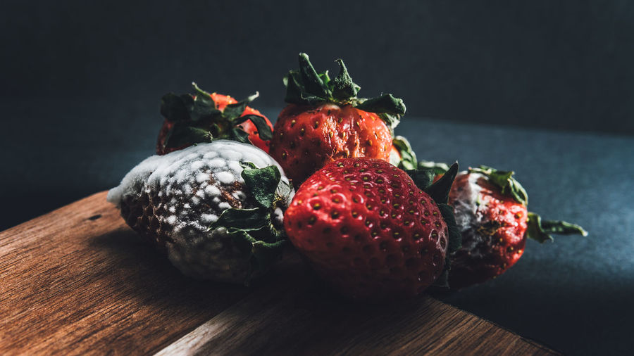 Close-up of strawberries on table against black background