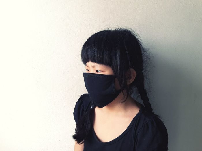 Girl Wearing Mask Looking Away While Standing Against Wall