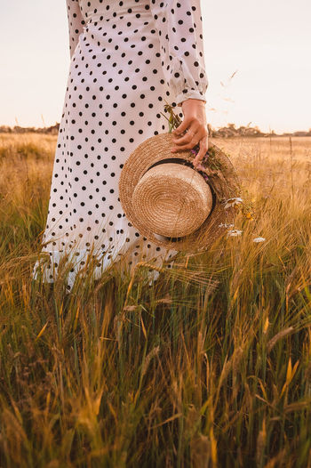 Woman holding hat on field