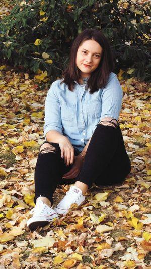 Portrait of teenage girl sitting on autumn leaves