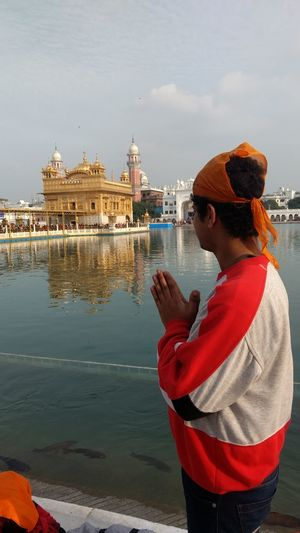 Boy praying at golden temple against sky