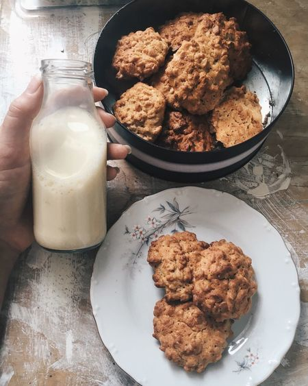 Cropped image of hand holding milk bottle by oatmeal cookies on table