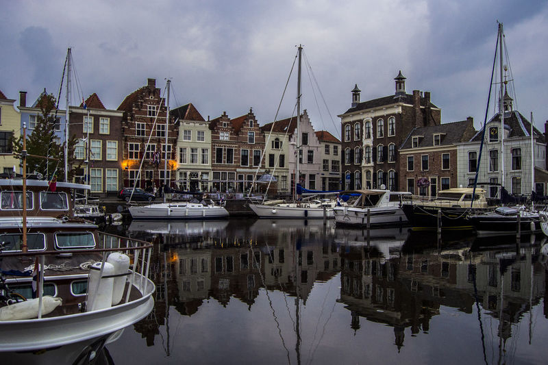 Buildings reflecting by boats on sea against cloudy sky