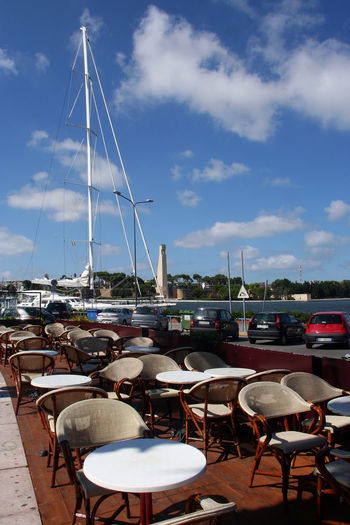Bar tables on the seafront Italia Puglia Puglia South Italy South Italy Blue Sky And Clouds Blue Sky And White Clouds Boat Chair Clouds Clouds And Sky Day Group Of Objects Nautical Vessel No People Outdoors Sea Seafront Seafront View Sky Table Travel Destination Water