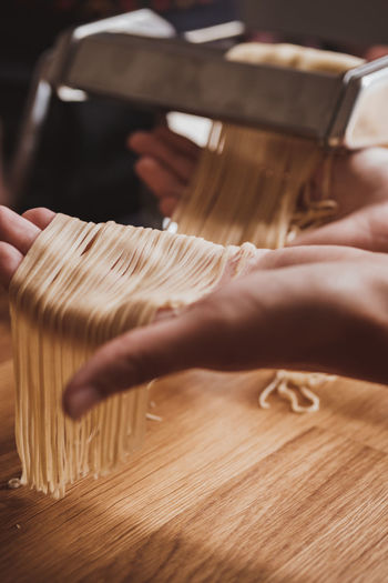 Cropped hand of woman preparing pasta with machine in kitchen