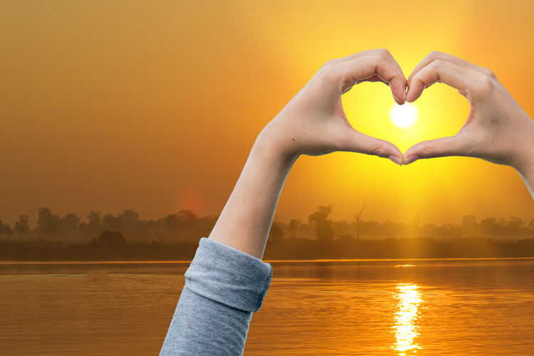 Hand shaping a love hand .and mountains surrounding. Sunrise background. love concept Heart Shape Water Sunset Sky Human Hand Real People Hand Positive Emotion One Person Love Human Body Part Nature Orange Color Lifestyles Emotion Lake Beauty In Nature Leisure Activity Sun Finger Lens Flare
