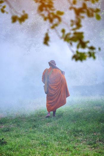 Rear View Of Monk Walking On Grassy Field