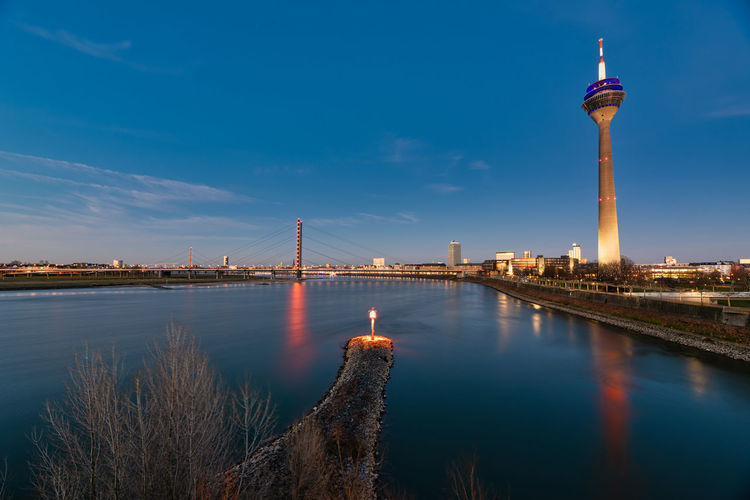 Duesseldorf, GERMANY - February 25, 2019: The lights of the old town and the TV tower gloom during the blue hour and create a vivid contrast TV-Tower Rhine Blue Hour Sundown Lights Vivid Urban Skyline Germany