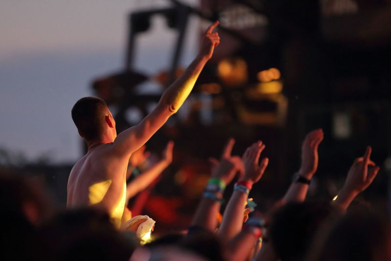 People With Arms Raised Enjoying At Music Concert