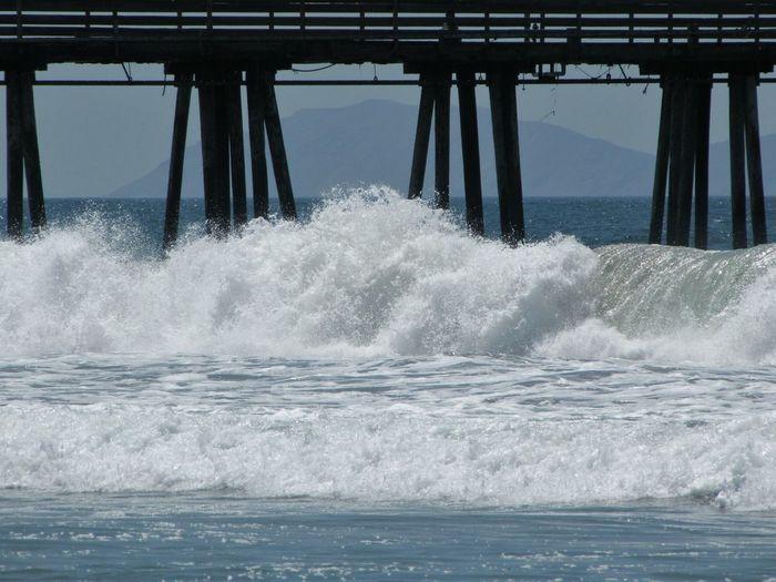 Waves splashing on pier in sea
