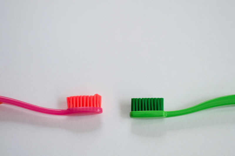 Toothbrush Indoors  Hygiene Close-up Dental Health Copy Space Two Objects No People Connection Routine Cleaning Green Color Studio Shot White Background Chores Bathroom Single Object Cable Still Life Choice Clean Power Supply