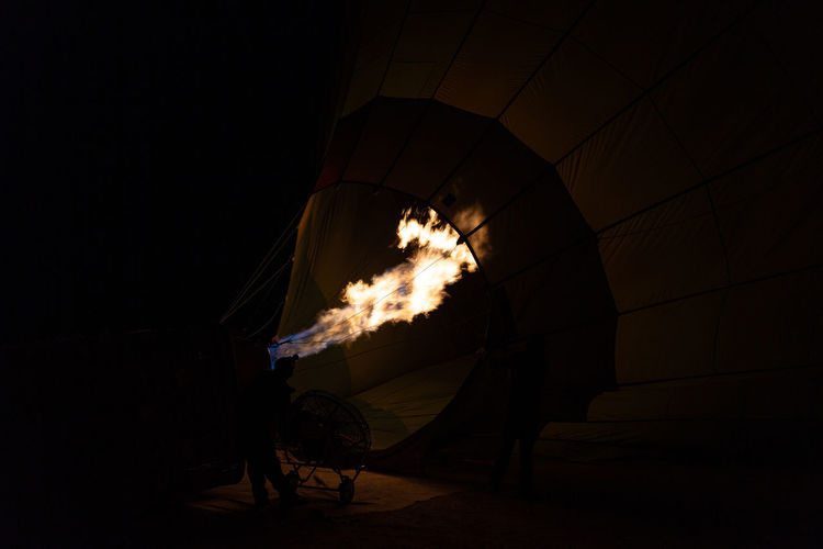 Silhouette of hot air balloon against black background