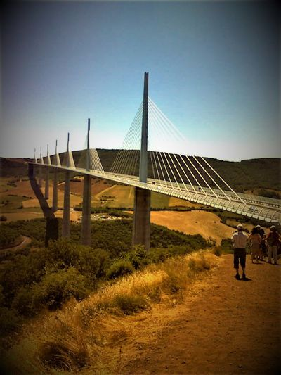 Hill side view of Millau Viaduct, South of France. Adult Architecture Built Structure Clear Sky Connection Day Full Length Grass Green Color Green Colours Landscape Leisure Activity Lifestyles Men Nature Outdoors People Real People Rear View Sky Standing Togetherness Two People Walking Women