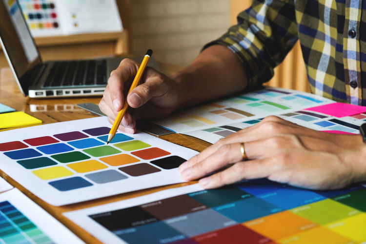 Midsection of businessman analyzing color swatch on desk in office