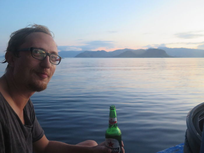 Portrait of smiling man drinking beer while sitting in boat at sea
