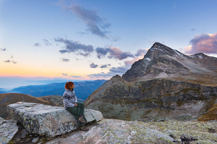 Hiker sitting on rock formation at mountain against sky during sunset