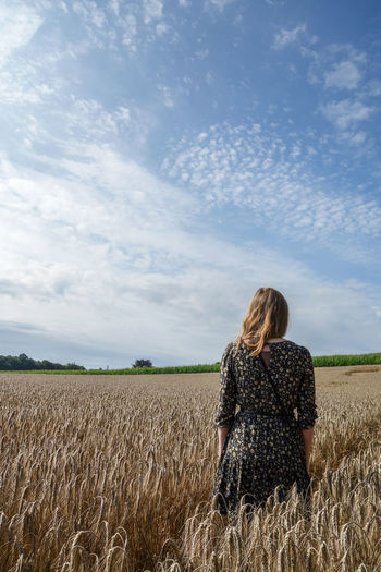 Rear view of woman walking by crops growing in farm against cloudy sky