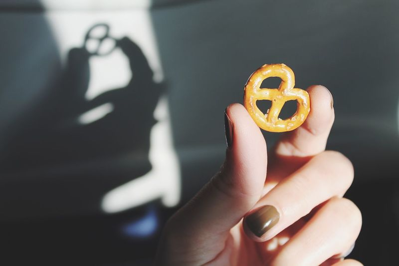 Cropped hand of woman holding pretzel against wall