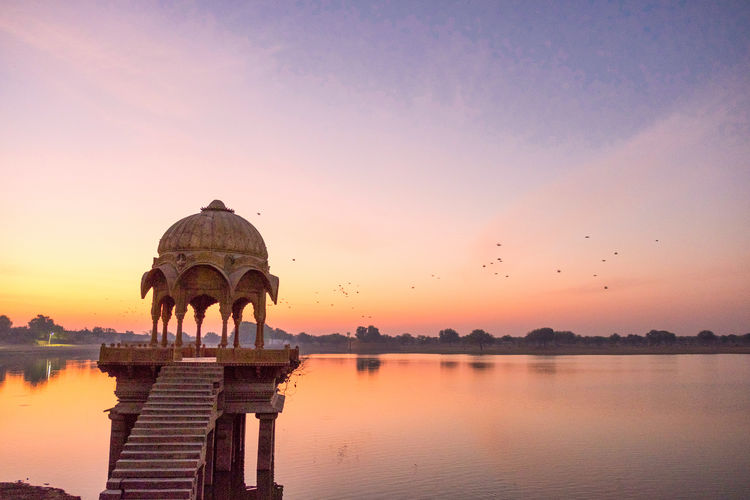 Sunrise over stone tower in Gadi Sagar lake, Jaisalmer, India. Animal Animal Themes Architecture Beauty In Nature Building Exterior Built Structure Dome Gadisagar Temple Gadisarlake Historical Idyllic Jaisalmer Lake Nature No People Orange Color Reflection Religion Scenics - Nature Sky Sunrise Sunset Water Waterfront