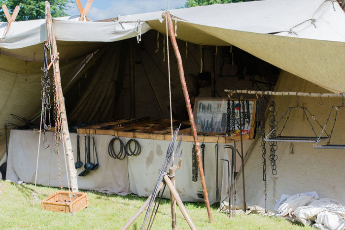 Camp and traders stand at a medieval festival Camp Campfire Castle Woman Chain Mail Coat Stand Event Fur History Knights Knights Time Market Stall Medieval Medieval Cooking Medieval Festival Medieval Market Medieval Spectacle Nostalgia Shield Storage Space Sword Sword Fight Viking